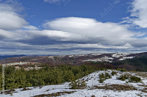 Majestic view of cloudy sky, winter mountain, snowy glade, residential district, conifer and deciduous forest from Plana mountain toward Balkan mountain or Stara planina, Bulgaria, Europe  - 188400578