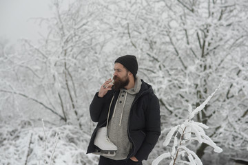 bearded man hold skate in snowy winter forest, christmas, smoking