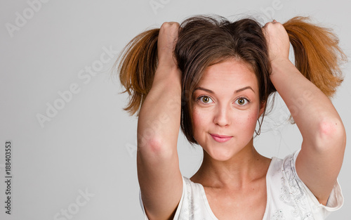 In de dag Kapsalon portrait of cheerful girl doing two ponytails on head with her hands