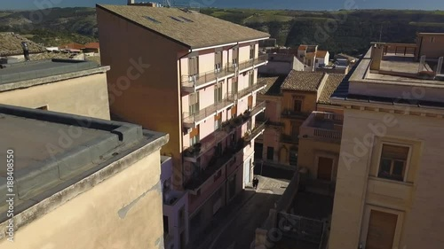 Poster flying backwards reveal of sculptures atop fascist Ragusa post office