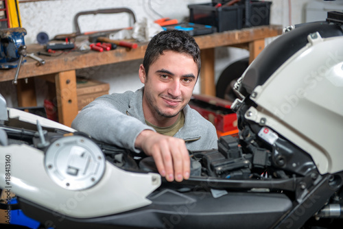 young man repairing the motorcycle