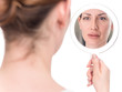 Beautiful woman looking at herself in the mirror. Isolated over white background.