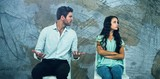 Composite image of couple sitting on chairs having argument