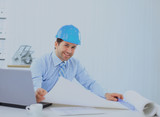 Architect looking working in office at desk. Wearing hardhat and taking notes on paper. - 188428579
