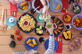 Top view of group of people having dinner together while sitting at wooden table. Food on the table. People eat fast food. - 188430310