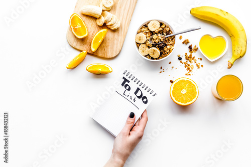 Morning habits of successful people. Healthy breakfast porridge with fruits and planning the day. White background top view copy space