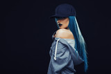 Young woman with cyan color hair in hoodie and cap - 188435384