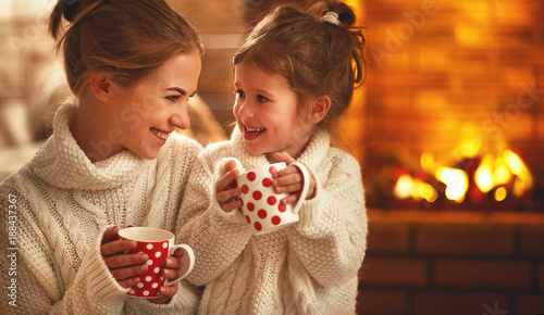 Leinwanddruck Bild family mother and child drinking tea and laughing on winter evening by fireplace.