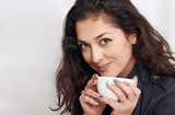 young woman portrait with cup of tea or coffee, beautiful face closeup with black curly hair