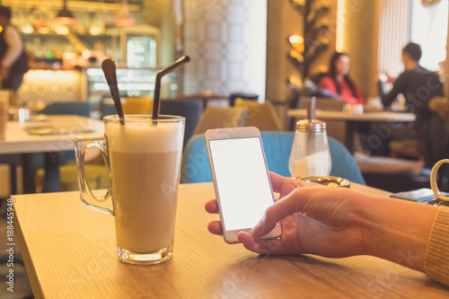 Female using smart phone and enjoying coffee in cafe