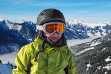 Portrait of boy in helmet and ski goggles on a sunny day in the mountains. Active outdoor childhood concept