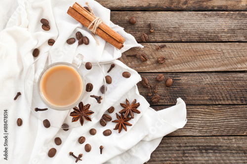 Coffee in a cup with spices and white cloth on a wooden background