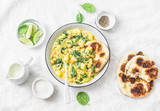 Chickpeas, spinach, potato curry plate and naan flatbread on white background, top view. Indian healthy vegetarian food - 188483143