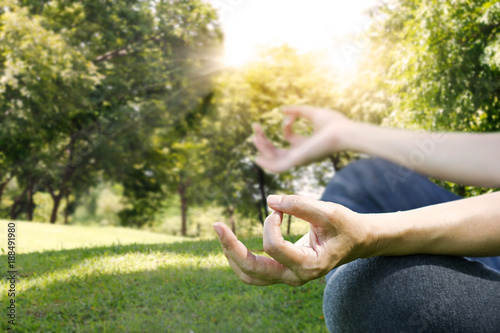 Wall mural Hands of woman meditating in a yoga pose on  park background