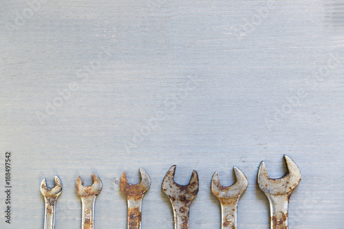 Different size wrenches on wooden background