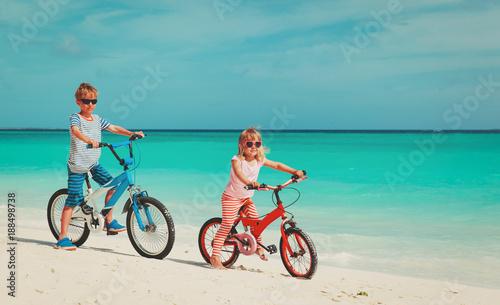 little boy and girl ride bike on beach