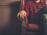 Young man sitting on a leather sofa - 188509117