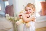 Glückliches Mädchen umarmt Teddybär