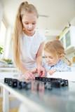Kinder bauen Reihe aus Dominosteinen