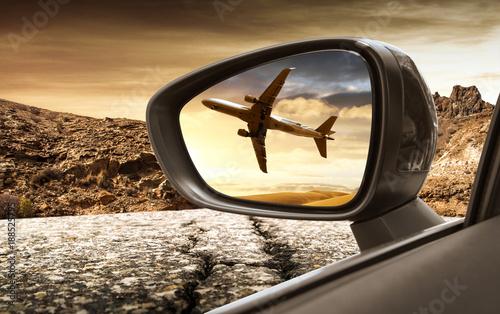 aereo di linea visto dallo specchietto retrovisore di un'automobile