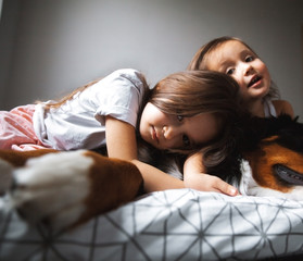 little girls sleeping in the bed with her dog