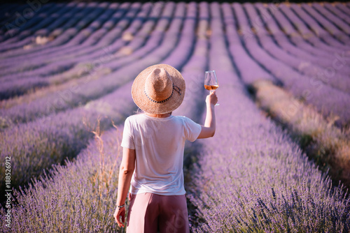 Young woman drink rose wine in the sunset lavender field, standing back to the camera, Provence, south France