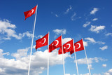 Turkish flags flutter in the wind against a blue sky. - 188538726