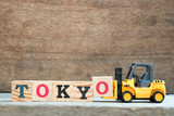 Yellow toy forklift hold letter block O to complete word Tokyo on wood background