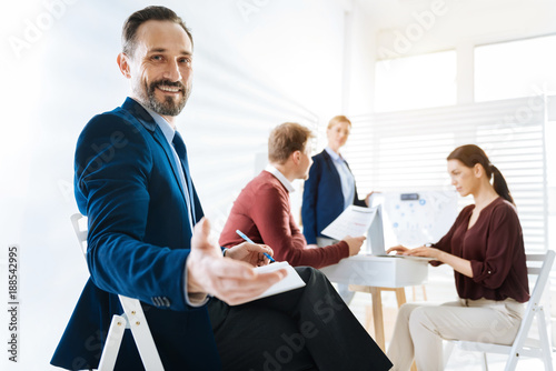 Enjoy us. Low angle of happy glad male colleague sitting on the chair while stretching hand and looking at the camera