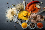 Various spices(pepper ground turmeric ginger cinnamon grass seasoning) in metal antique spoons on stone beton table. Top view - 188547182