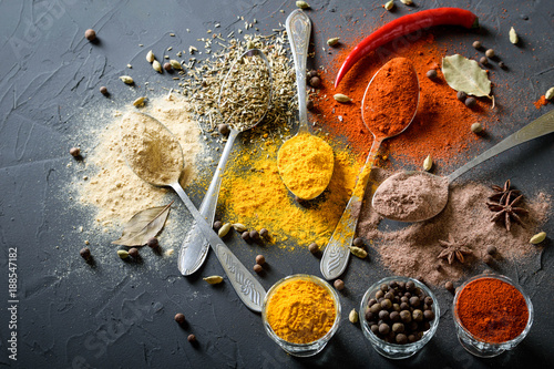 Poster Various spices(pepper ground turmeric ginger cinnamon grass seasoning) in metal antique spoons on stone beton table. Top view