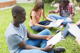 Multi ethnic teenagers friends making school tests outdoor, seated on a park