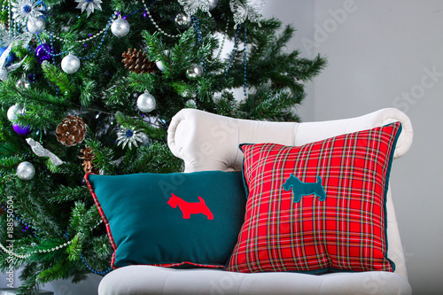Foto Murales pillow with image of a dog lying on the chair. Background Christmas tree
