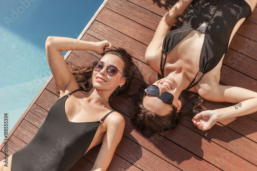 high angle view of attractive young women in swimsuits lying at poolside