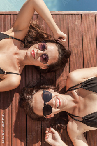 top view of smiling young women in swimsuits lying on poolside