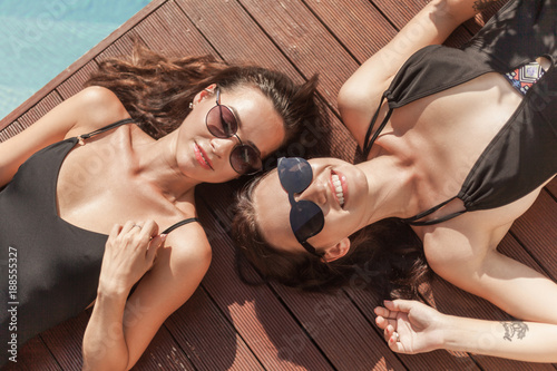 top view of happy young women in swimsuits lying on poolside