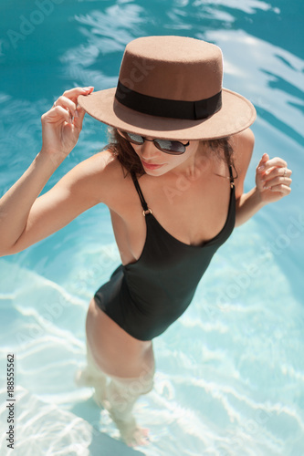 high angle view of young woman in swimsuit and hat standing in pool