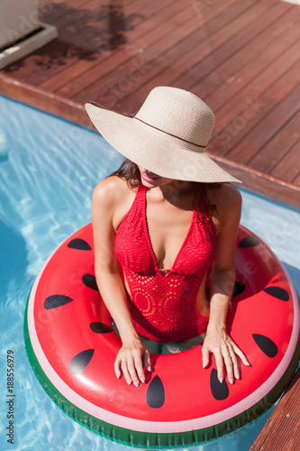 high angle view of young woman in swimsuit standing in swimming pool with inflatable ring