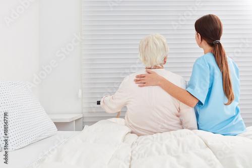 Pflegerin hilft Seniorin aus dem Bett in der Reha
