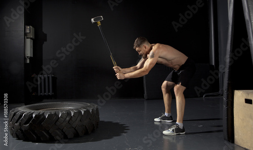 Man hitting wheel tire with hammer sledge