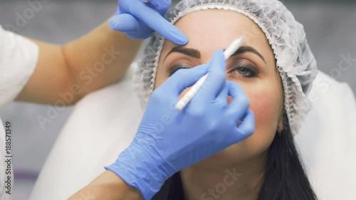 Beautician draws zones on face for future botox procedure © oles_photo