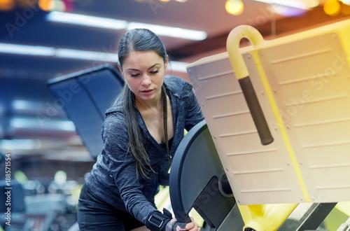 Fridge magnet young woman adjusting leg press machine in gym