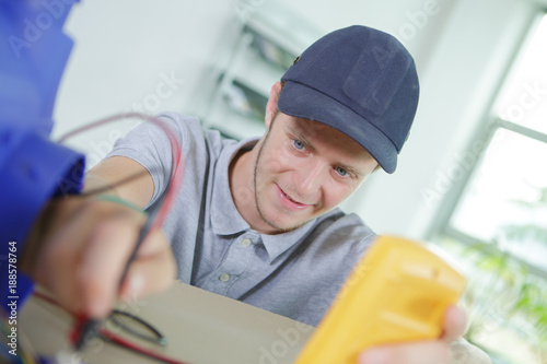 young electrician fixing a cable