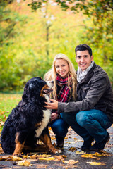 Happy couple with dog enjoying autumn in nature