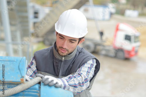 Foto Murales Man with compressor on construction site