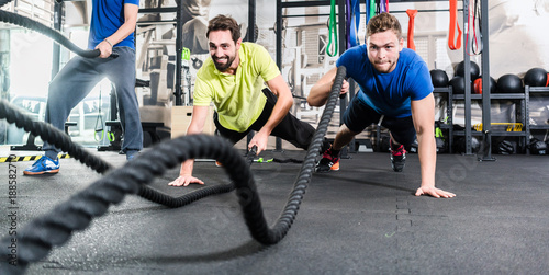 Poster Men with battle rope in functional training fitness in gym