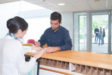 man checking in at reception desk - 188589155