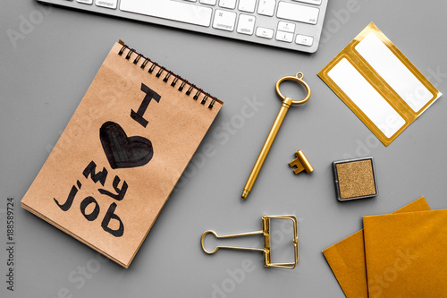 Find dream job. Handwritten motto I love my job in notebook near stationery on grey background top view