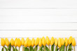 Yellow tulips border on white wooden background. Copy space, top view. - 188590955