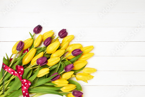 Colorful tulips bouquet decorated with red ribbon on white wooden background. Greeting card Copy space, top view.